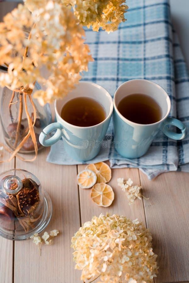 Dos tazas de té caliente en una servilleta azul de lino Hortensia secada, limón, castaña, canela fotos de archivo libres de regalías