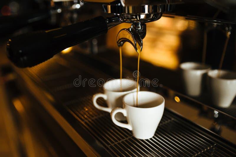 Dos tazas del café express en la máquina del café imagen de archivo