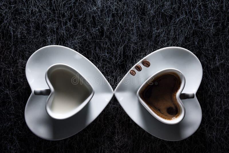 Dos tazas en forma de corazón con café sólo y la leche que señalan el uno al otro, con tres granos de café fotografía de archivo libre de regalías