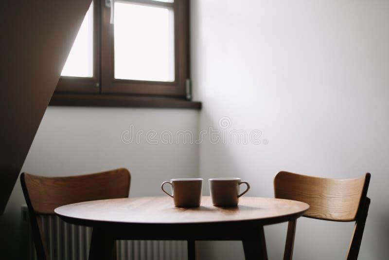Dos tazas en la tabla de madera Comedor con la tabla y dos sillas Interior nórdico escandinavo mínimo moderno Caf? de la ma?ana imagenes de archivo