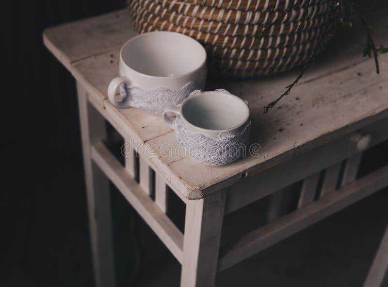 Dos tazas en la tabla vieja del vintage Estilo rústico, interrior del país imagen de archivo