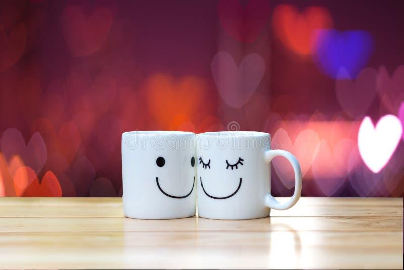Dos tazas felices en la tabla de madera con el fondo del bokeh del corazón fotografía de archivo