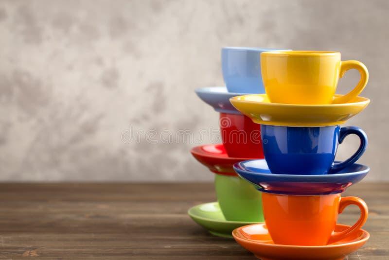 Dos tazas multicoloras de las pilas en la tabla del lado derecho imagenes de archivo