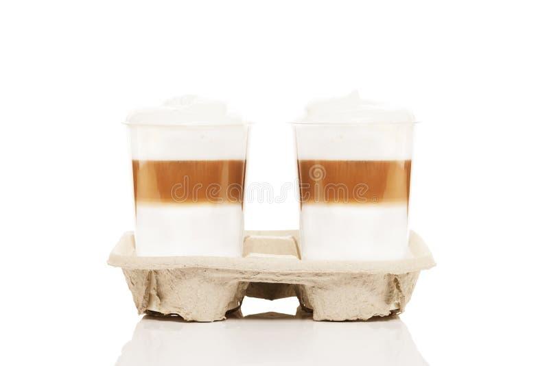 Dos tazas plásticas con el macchiato del latte a ir imagen de archivo