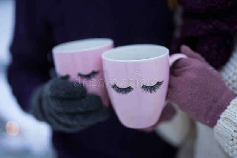 Dos tazas rosadas con las pesta?as en las manos de la gente foto de archivo
