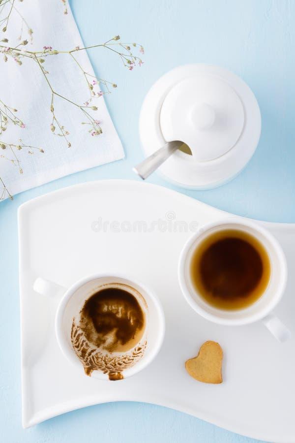 Dos tazas vacías de café y de galleta en forma de corazón en una bandeja imagenes de archivo