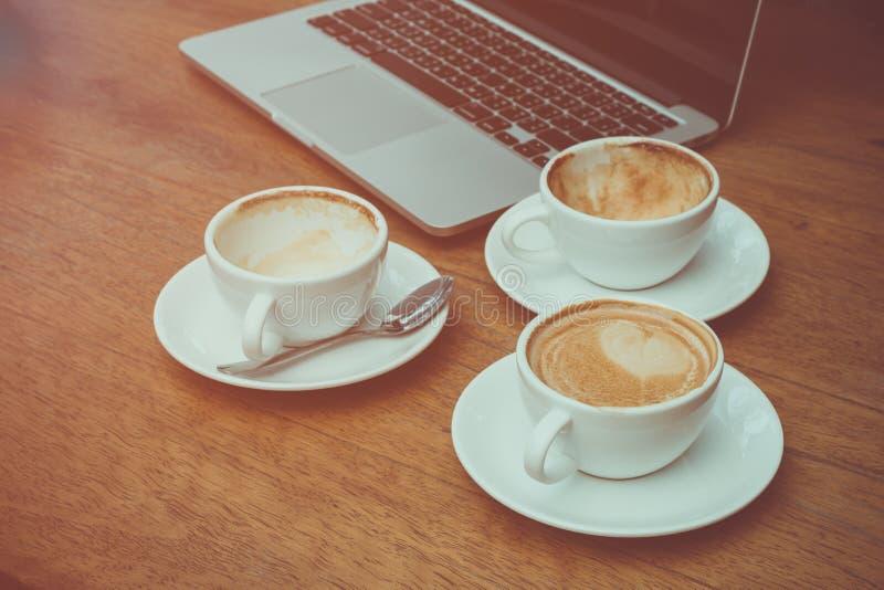 Dos tazas vacías y taza de café llena que colocan junto foto de archivo libre de regalías