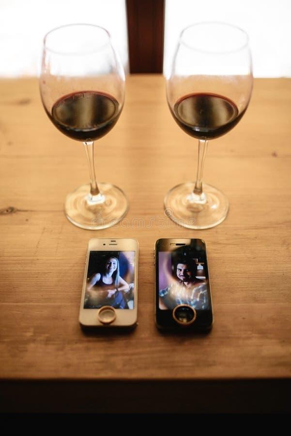 Dos teléfonos, anillos y dos vidrios de vino en una tabla imagen de archivo
