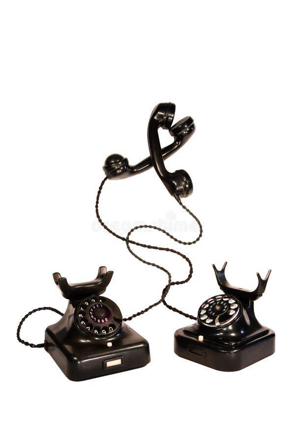 Dos teléfonos negros de la vendimia enredados imágenes de archivo libres de regalías