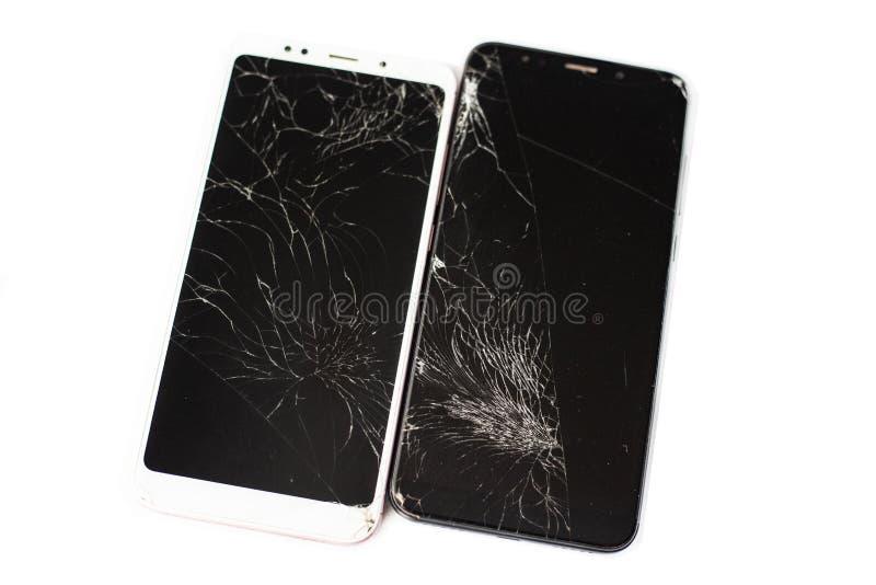 Dos teléfonos quebrados de blanco y de negro en un fondo blanco vidrio agrietado de la pantalla táctil del aislante de la pantall fotos de archivo