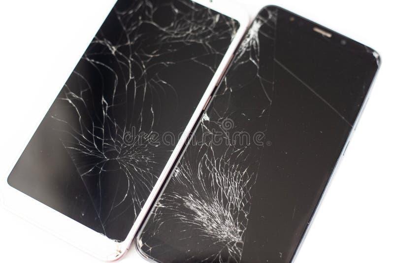 Dos teléfonos quebrados de blanco y de negro en un fondo blanco vidrio agrietado de la pantalla táctil del aislante de la pantall imagenes de archivo