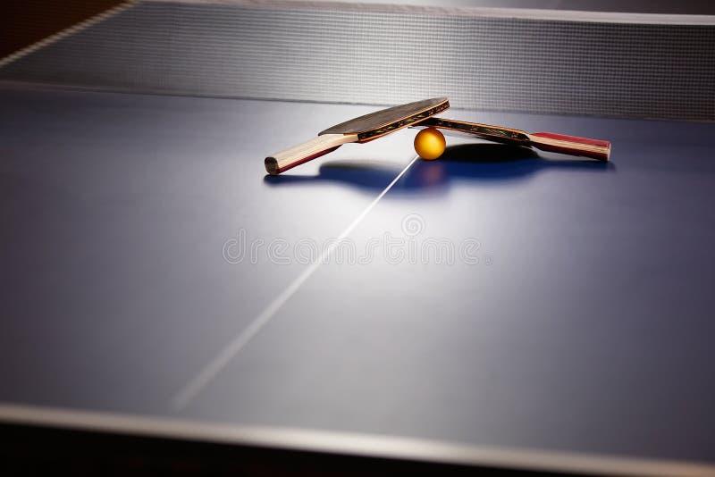 Dos tenis de mesa o estafas y bolas del ping-pong en una tabla azul w foto de archivo