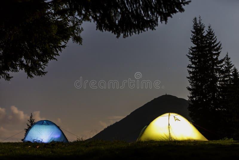 Dos tiendas turísticas brillantemente iluminadas sobre el bosque verde de hierba despejado en la montaña oscura y azul claro ciel foto de archivo