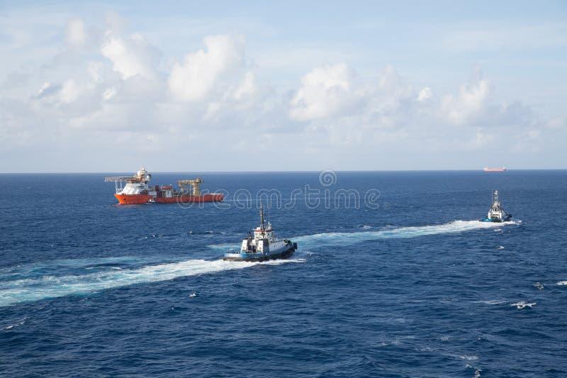 Dos tirones y petrolero anaranjado en el mar azul fotos de archivo