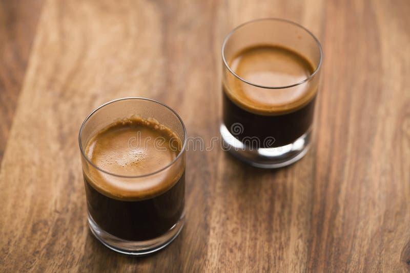 Dos tiros de café express en la tabla de madera imagenes de archivo