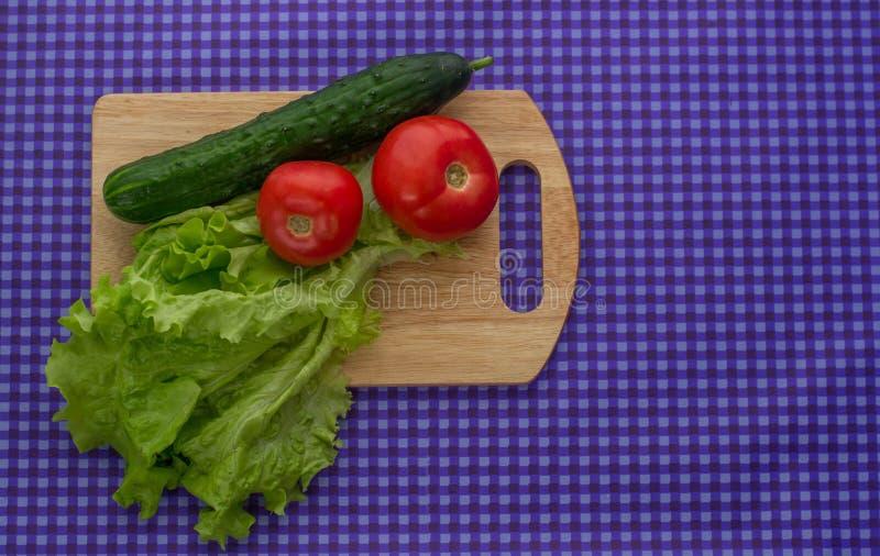 Dos tomates, ensalada y un pepino en un tablero de madera en un fondo púrpura fotos de archivo libres de regalías