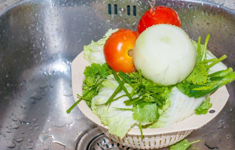 Dos tomates frescos rojos, el perejil verde, la cebolla grande y la col están siendo limpiados por el agua imagen de archivo libre de regalías