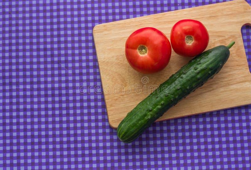 Dos tomates y un pepino en un tablero de madera en un fondo púrpura foto de archivo libre de regalías