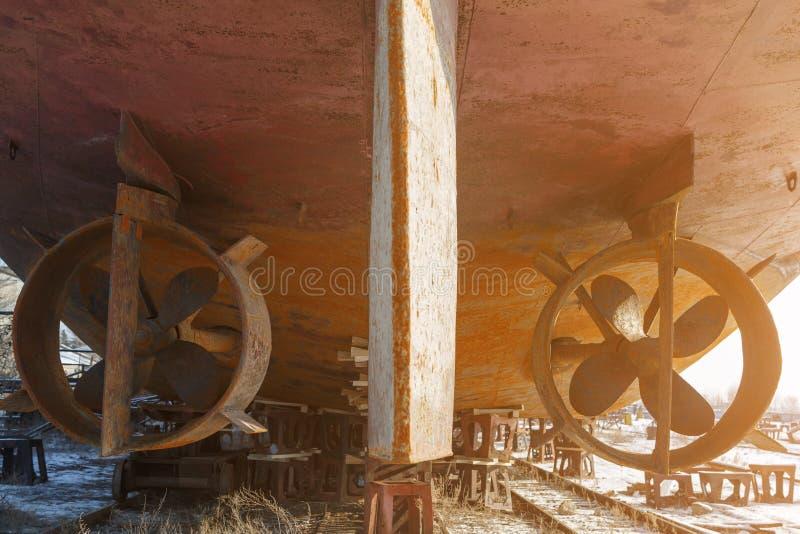 Dos tornillos oxidados en la boca que pertenece a la nave, que se coloca en una dique seco en invierno fotografía de archivo libre de regalías
