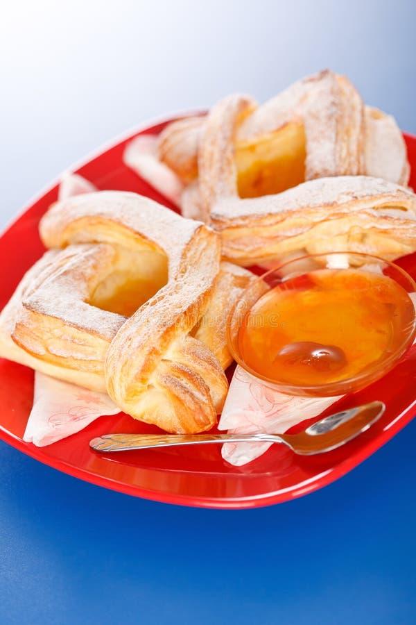 Dos tortas y atascos del melocotón en la placa foto de archivo libre de regalías