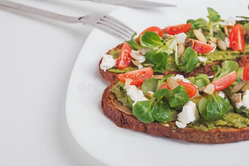 Dos tostadas del aguacate con el queso feta, los tomates de cereza y los verdes imagenes de archivo