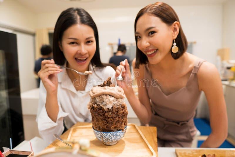 Dos trabajadoras hermosas comen el chocolate Bingsu imagen de archivo libre de regalías