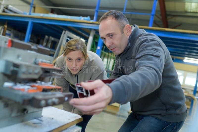 Dos trabajadores calificados que trabajan en la máquina en fábrica fotografía de archivo libre de regalías
