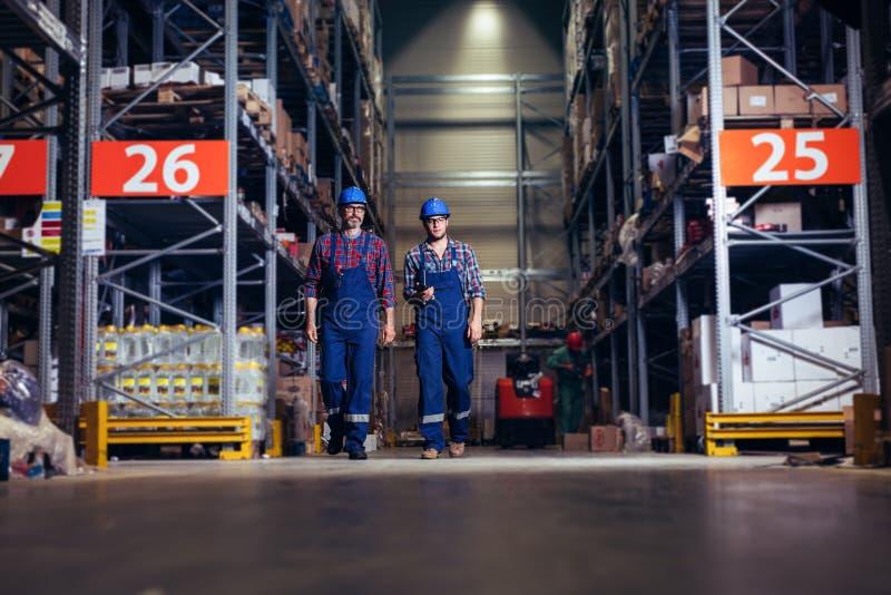 Dos trabajadores con los cascos en las cabezas que caminan en almacén imagenes de archivo