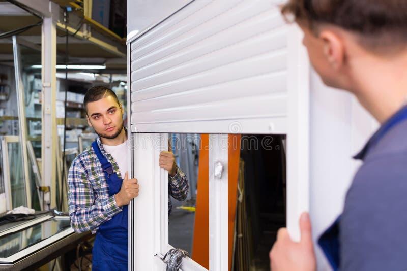 Dos trabajadores cuidadosos que examinan ventanas imagen de archivo libre de regalías