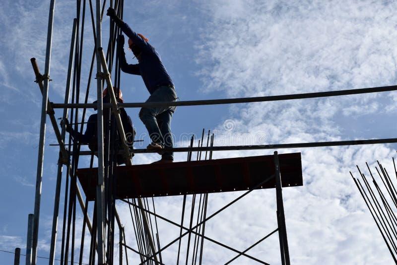 Dos trabajadores de acero de la construcción filipina que montan las barras de acero en el edificio alto sin los trajes protector imágenes de archivo libres de regalías