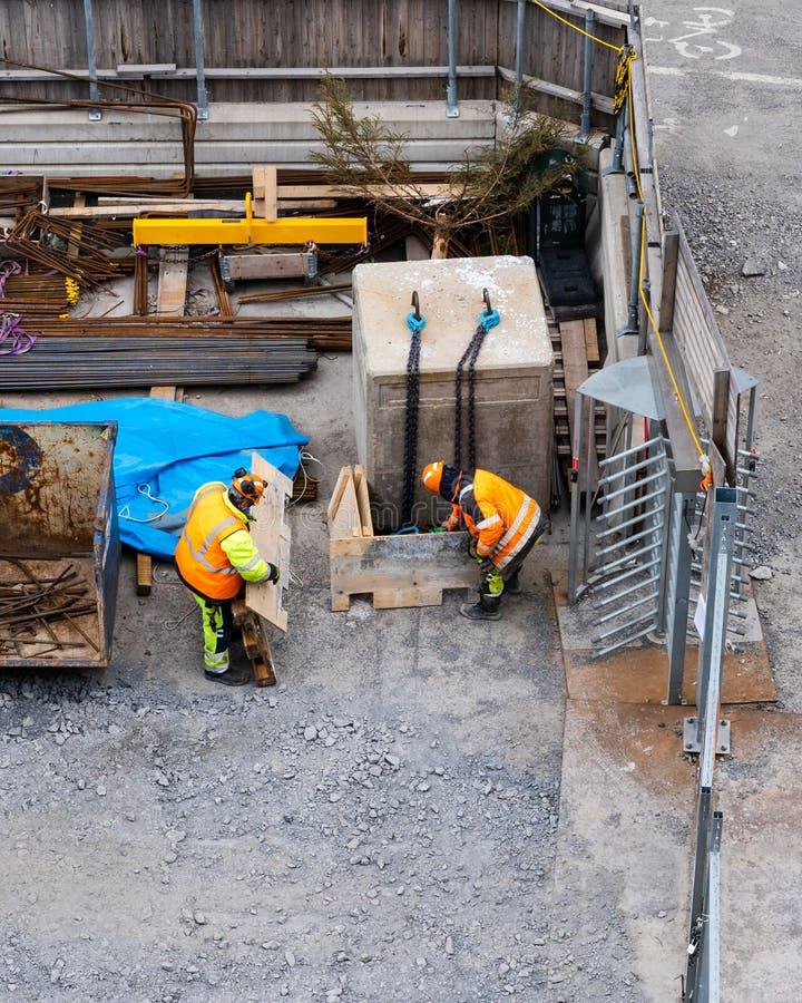 Dos trabajadores de construcción en el almacén de los sitios que busca para el material, Estocolmo Suecia fotos de archivo libres de regalías