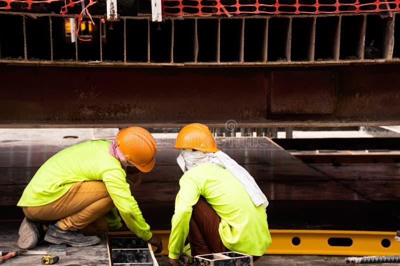 Dos trabajadores de construcci?n que llevan la camisa verde de la seguridad que se sienta y que comprueba mirando el frente compr foto de archivo