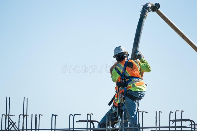 Dos trabajadores de construcción vierten el cemento en rebar fotos de archivo