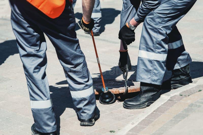 Dos trabajadores de servicio de gas de la emergencia, comprobando la concentración de gas en la alcantarilla fotografía de archivo libre de regalías