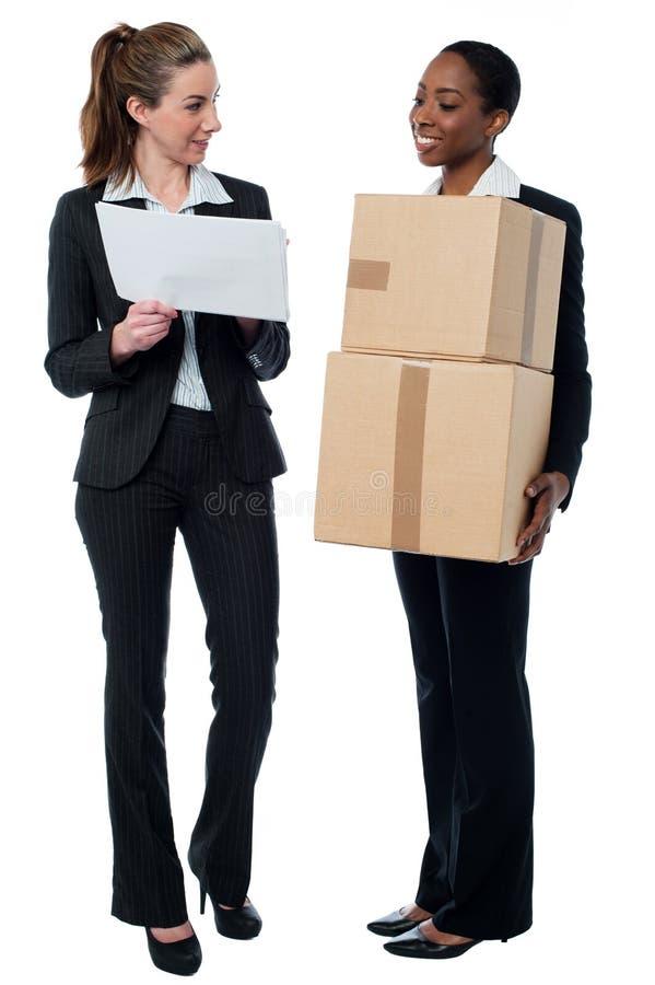 Dos trabajadores de sexo femenino que discuten los detalles comunes imágenes de archivo libres de regalías