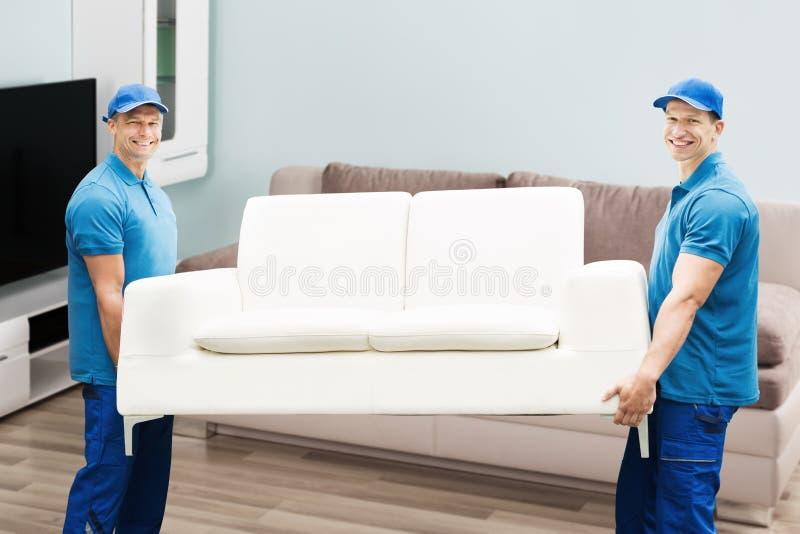 Dos trabajadores de sexo masculino que llevan el sofá fotos de archivo