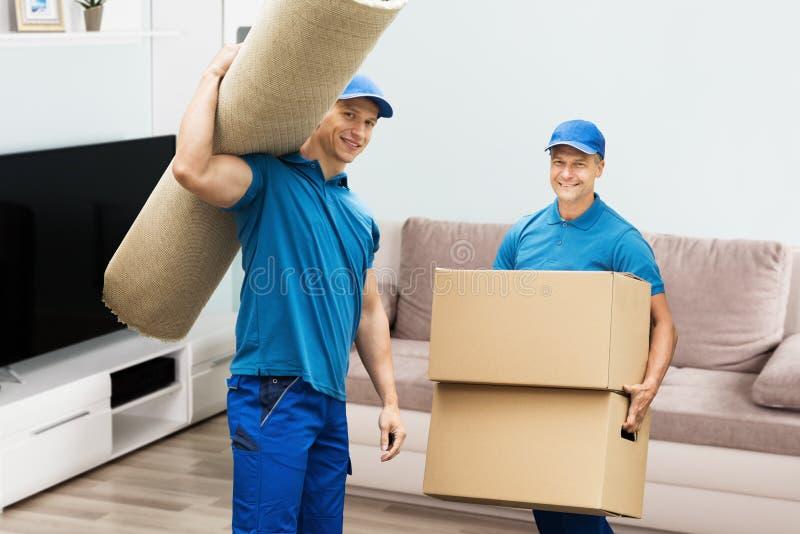 Dos trabajadores de sexo masculino que llevan las cajas de la alfombra y de cartón imagenes de archivo