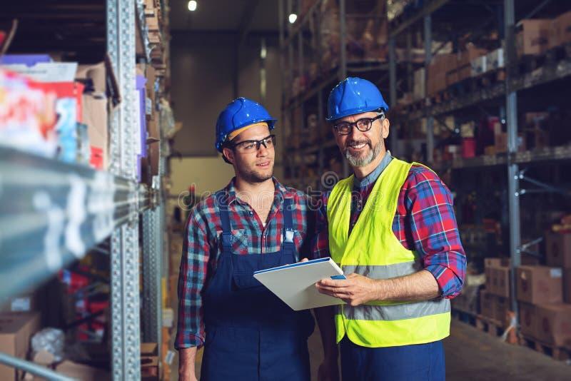 Dos trabajadores del almac?n que completan el documento imagen de archivo