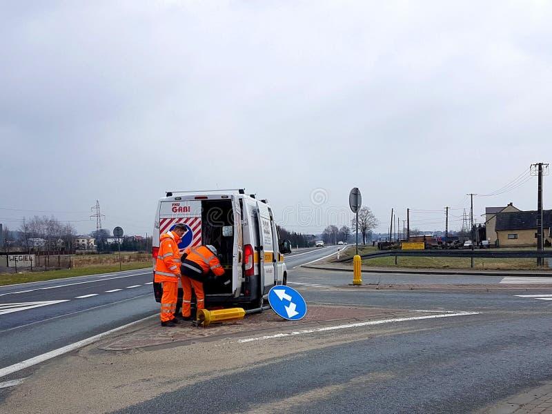 Dos trabajadores del servicio del camino vinieron trabajar en su coche oficial para reparar una señal de tráfico quebrada en la c fotografía de archivo