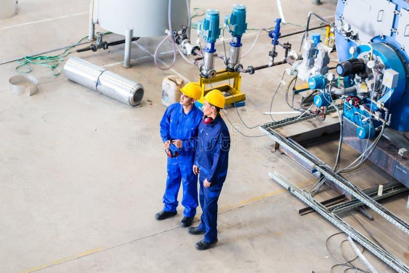 Dos trabajadores en la discusión industrial de la fábrica imágenes de archivo libres de regalías