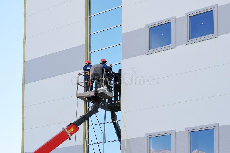 Dos trabajadores en la plataforma de la elevación foto de archivo libre de regalías