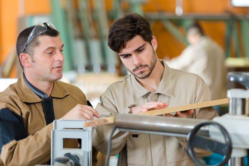 Dos trabajadores en taller de los carpinteros fotografía de archivo