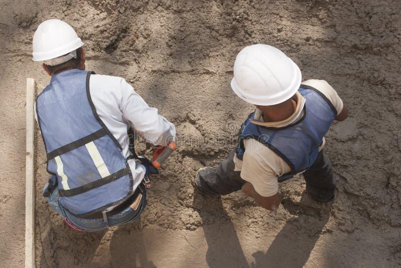 Dos trabajadores en un emplazamiento de la obra foto de archivo