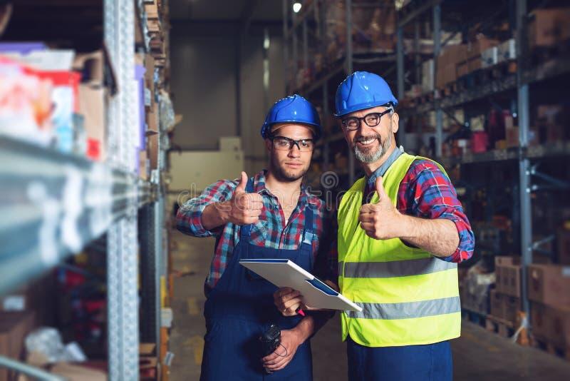 Dos trabajadores en uniformes en warehouse imagenes de archivo