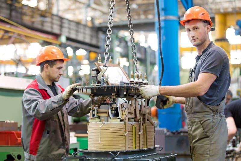 Dos trabajadores industriales que montan el transformador de poder en el taller de la fábrica del transportador imagenes de archivo