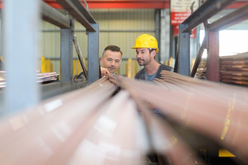 Dos trabajadores que buscan perfiles específicos del pvc en almacén de la fábrica imagenes de archivo