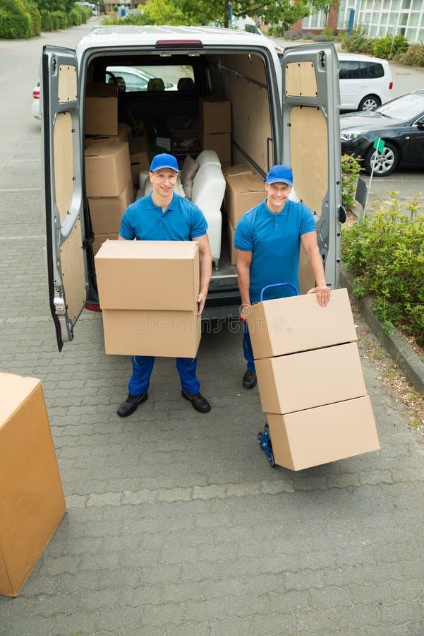 Dos trabajadores que cargan las cajas de cartón en el camión fotos de archivo libres de regalías