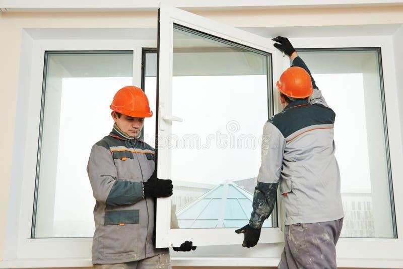 Dos trabajadores que instalan la ventana foto de archivo