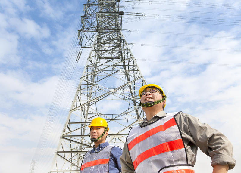 Dos trabajadores que se colocan antes de torre de la corriente eléctrica imagenes de archivo