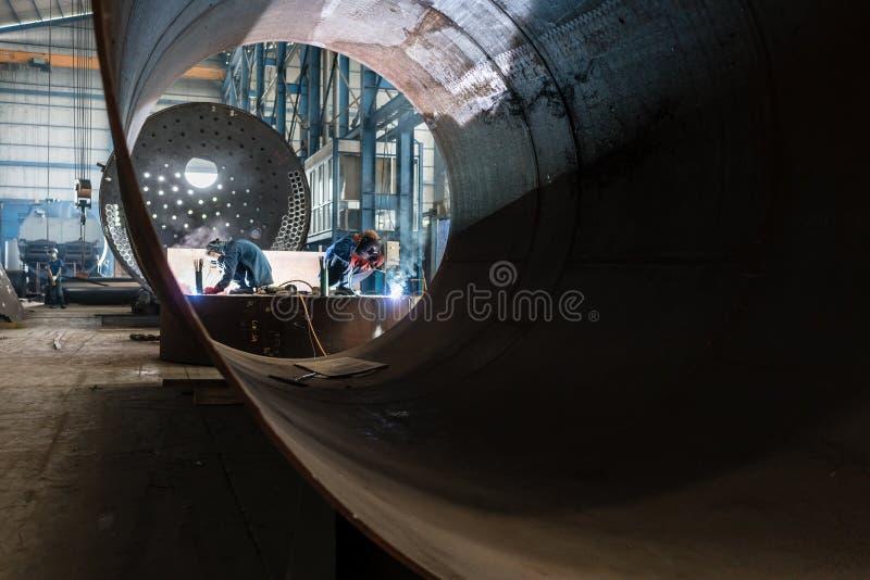 Dos trabajadores que sueldan con autógena en calderas de una fabricación de la fábrica foto de archivo